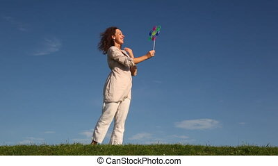 Woman stands and holds toy windmill spinning at wind