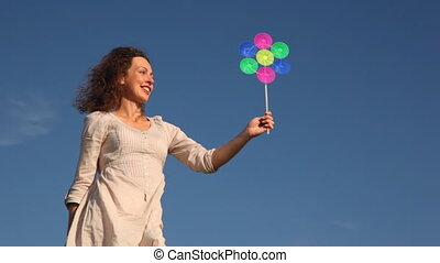 Woman stands and holds toy windmill - pretty young woman...