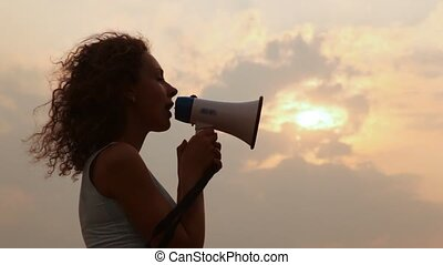 woman stands and tells something in megaphone
