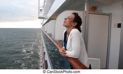 woman stands at handrail looks at waves from board of ship -...