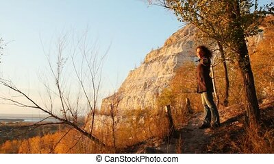 woman stands having stretched hands on footpath against mountain and wood in autumn