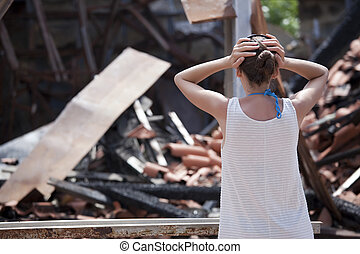 woman stands in front of burned out house - woman standing...