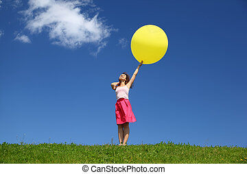 Woman stands in summer in field holds balloon and looks in...