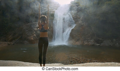 Woman Stands in Yoga Position against Waterfall - closeup...
