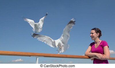 Woman stands near fence and feeds several gulls by bread