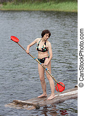 woman stands on a wooden raft
