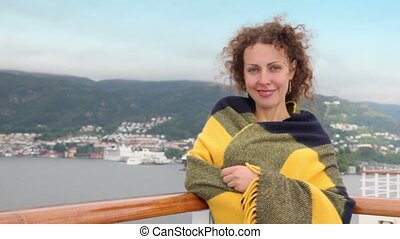Woman stands on deck near fence and smile during cruise -...