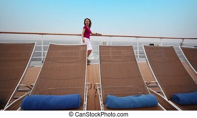 Woman stands on deck near fence behind few deckchairs during cruise