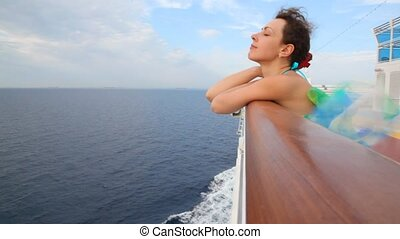 woman stands on deck of cruise ship