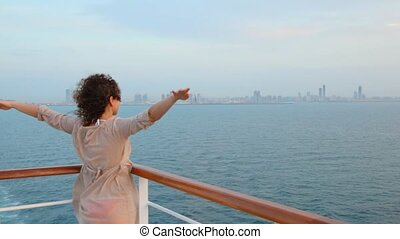 woman stands on deck of ship sailing out city