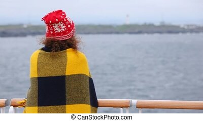 Woman stands on deck of vessel having turned back and having...