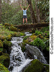 Woman Stands on Log Bridge and Power Poses