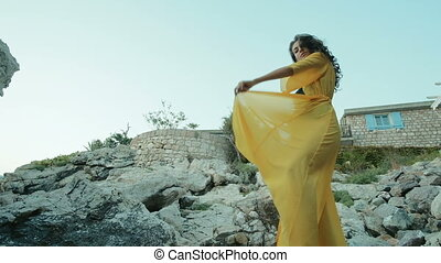 Woman stands on rocks waving a hem of a long yellow attire....