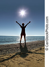 Woman stands on toes ashore opposite sun , heaving up hands...