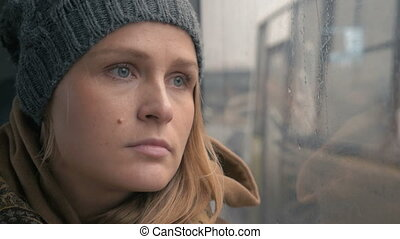 Woman staring through the wet bus window