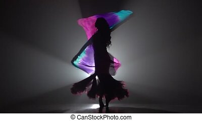 Woman starts dancing belly dance with multicolored shawl....