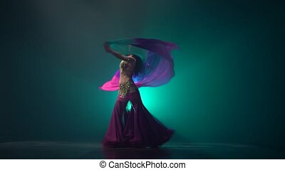 Woman starts dancing belly dance with shawl. Smoke...