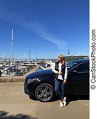 Woman staying near luxury black car parked near yachts marine