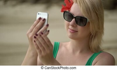 Woman staying on a beach and taking photo