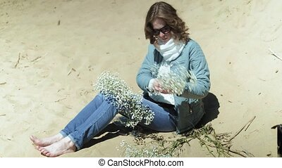 Woman staying on a beach with flower at the sunny day 4k