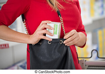 Woman Stealing Capsule Packet At Supermarket - Midsection of...