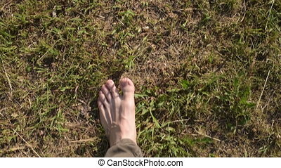 Woman stepping barefoot on grass. Shot from hands, slow...