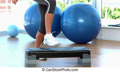 Woman stepping on exercise step