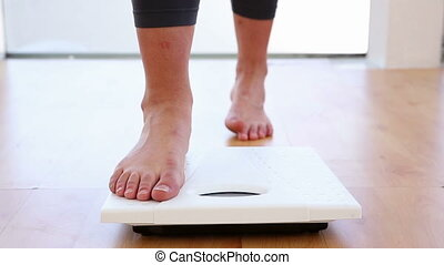 Woman stepping on scales at the gym