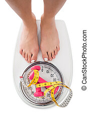 Woman Stepping On Weight Scale With Dumbbells And Tape ...