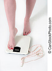 Woman stepping onto a bathroom scale - woman stepping onto a...