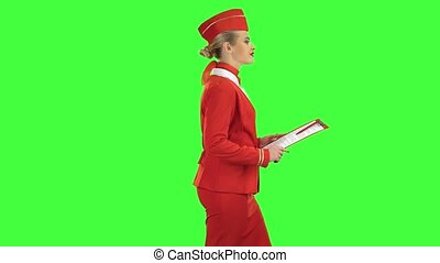 Woman steps along with a red folder in her hands. Green screen. Side view