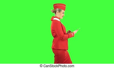 Woman steps with the phone and writes a message . Green screen. Side view