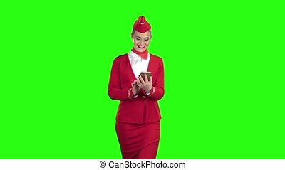 Woman steps with the phone and writes a message . Green screen . Slow motion