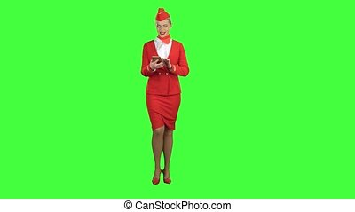 Woman steps with the phone and writes a message . Green screen