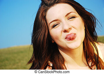 Woman sticking her tongue out - A beautiful young woman...