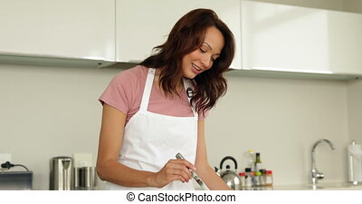 Woman stirring saucepan with lots of vegetables on counter...