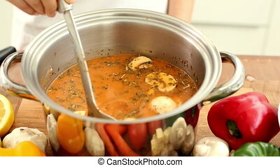 Woman stirring soup in a saucepan at home in the kitchen