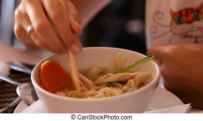 Woman stirring the pho ga Vietnamese chiken noodles soup...