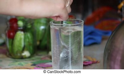 Woman stirs the marinade in a glass. Pickling cucumbers and...
