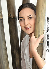 Woman stood by bamboo