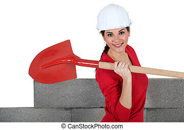 Woman stood by unfinished wall with spade