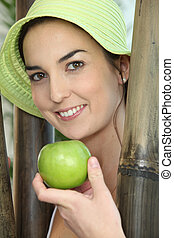 Woman stood by wooden poles holding a green apple