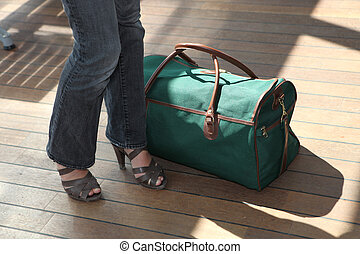 Woman stood next to baggage