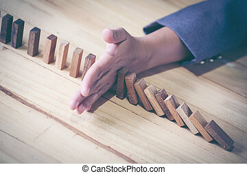 Woman stopping domino effect on wooden table. Business success concept. Copy space.