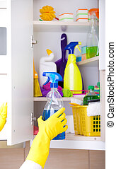 Woman storing cleaning tools in pantry - Woman with safety...
