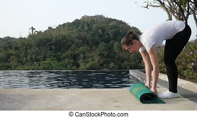 Woman straightens gymnastic mat outdoors. Slow motion.