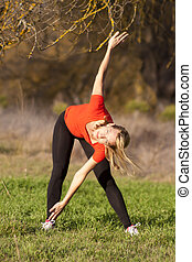 Beautiful young woman streching in the clearing.