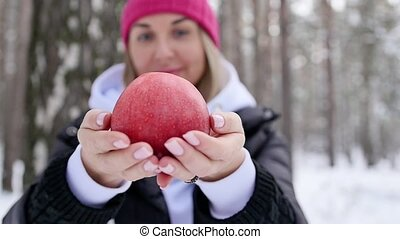 Woman stretches a red apple to the camera against the background of a winter snow-covered forest