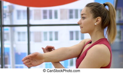 Woman stretches muscles of one hand before physical exertion...