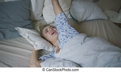 Woman stretching arms in bed - Attractive young woman in...